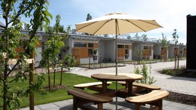Bild på en gemensam uteplats på ett bostadsområde. Bordet har ett parasoll och i bakgrunden ser du ett envånings radhus.