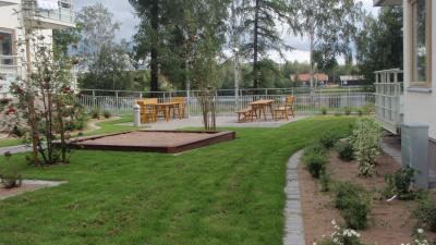 Bild på en uteplats mellan två lägenhetshus. Två bord med bänkar och en sandlåda.