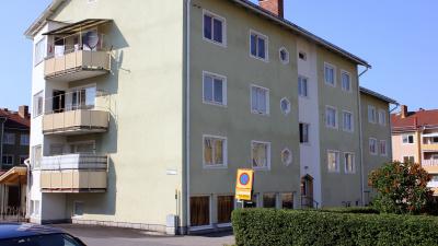Grönt flerbostadshus i puts i tre våningar.