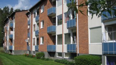 Bild på trevånings lägenhets hus i tegel med blåa balkonger.