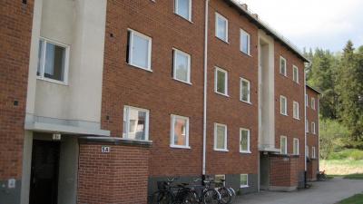 Bild på trevånings lägenhetshus i tegel.