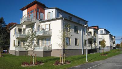Två lägenhetshus i tre våningar i vit puts och balkonger av stål.