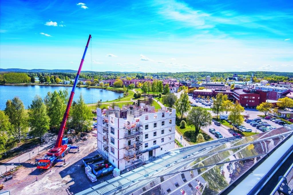 Bild på uppbyggnad av hyreshus, byggkran och blå himmel