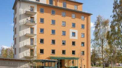 Lägenhetshus i sju våningar i gul och vit puts.