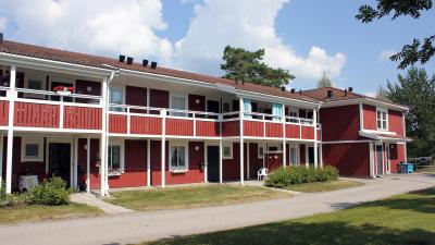 Bild på tvåvånings lägenhetshus i två våningar. Rött trähus med egna ingångar ifrån loftgång.