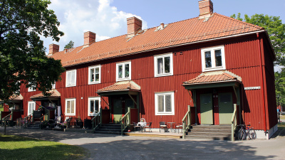 Bild på lägenhetshus i två våningar. Rött trähus med egen ingång.