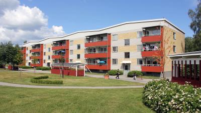 Bild på lägenhetshus i gult och vitt tegel och röda balkonger. Grön gräsmatta och lekande barn på gården.