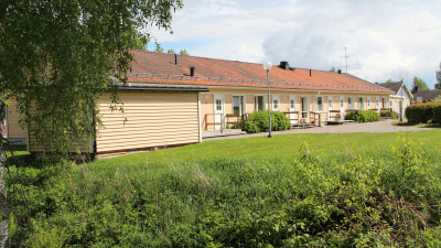 Bild på envånings flerbostadshus och gräsmatta i förgrunden