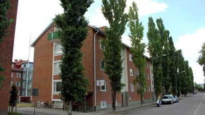 Tegelröda lägenhetshus i tre våningar.