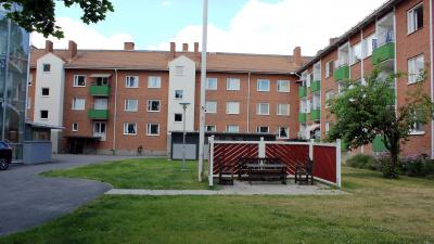 Lägenhetshus i tre våningar i röd tegel.