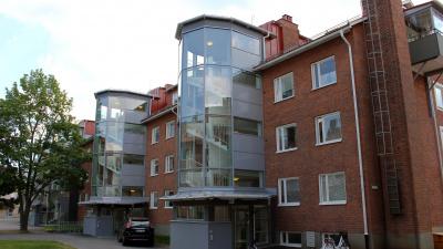 Lägenhetshus i tre våningar i röd tegel och inglasat trapphus.