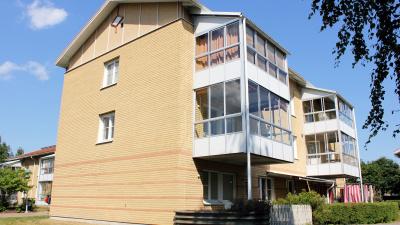 Bild på ett lägenhetshus i tre våningar i ljust tegel.