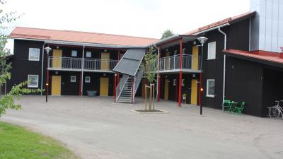 Lägenhetshus med svart träpanel. Egna entréer ifrån loftgång.