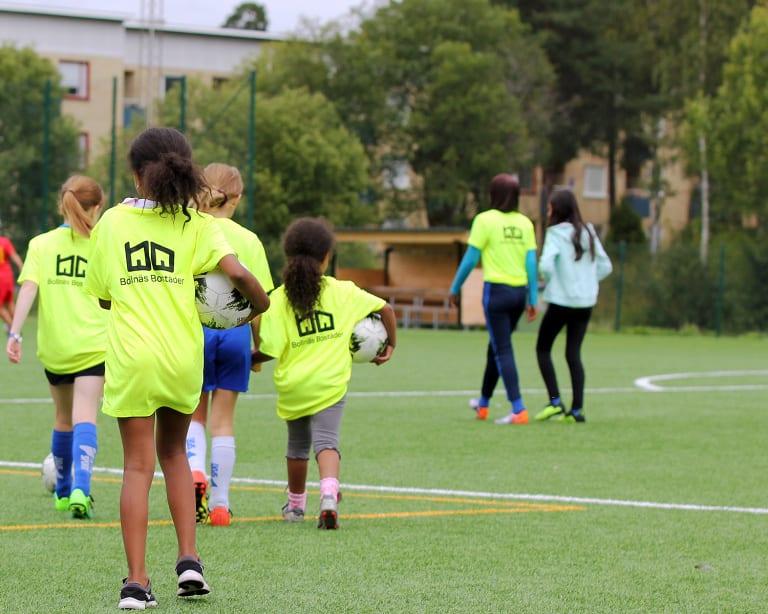 Bild tagen bakifrån på tjejer som håller i fotboll