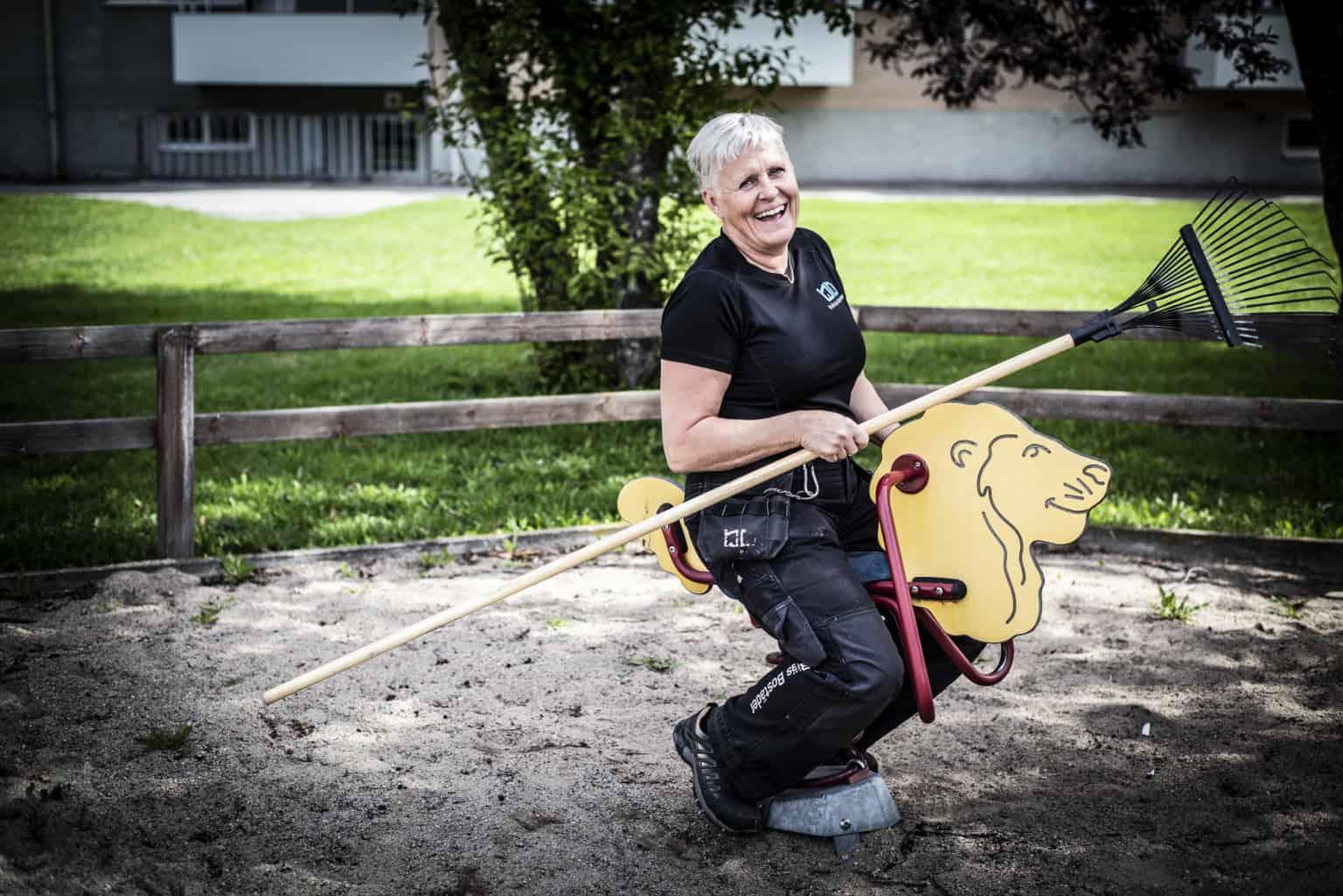 Glad fastighetsskötare som sitter på en gunghäst i en lekpark