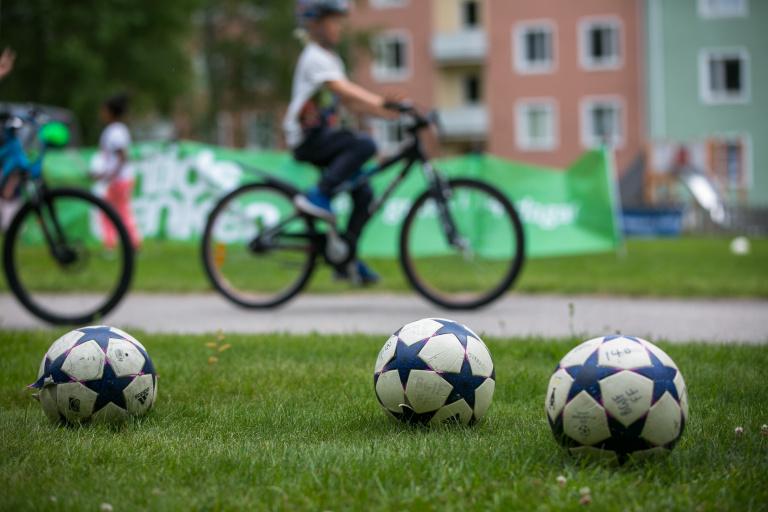 Bild på två fotbollar i förgrunden och ett barn på cykel i bakgrunden