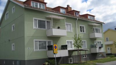 Bild på grönt lägenhetshus i puts