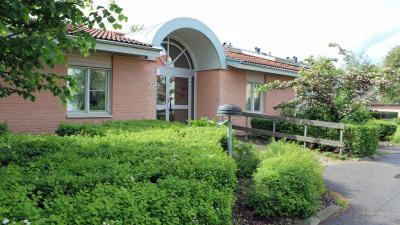 Bild som visar entrén till ett enplans ljusrött tegelhus med buskage på båda sidor om entrén.