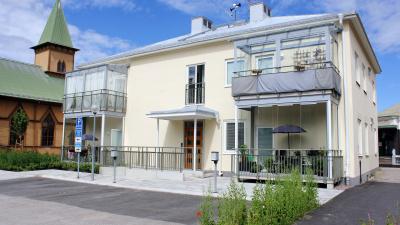 Litet flerbostadshus i ljusgul stenputs. Huset har två våningar och har inglasade balkonger.