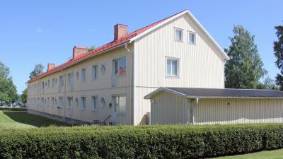 Flerbostadshus i två våningar med gul träfasad.