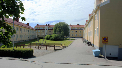 Bild på en innergård med en grön gräsmatta och en gungställning. Innergården är omsluten av tre flerbostadshus.