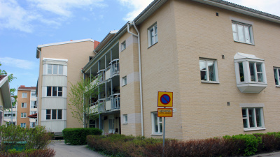 Lägenhetshus i ljust tegel. Huset har tre våningar och loftgång.